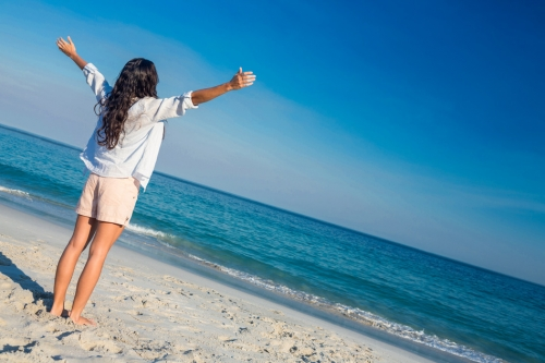 Happy woman with arms outstretched at the beach on a sunny day